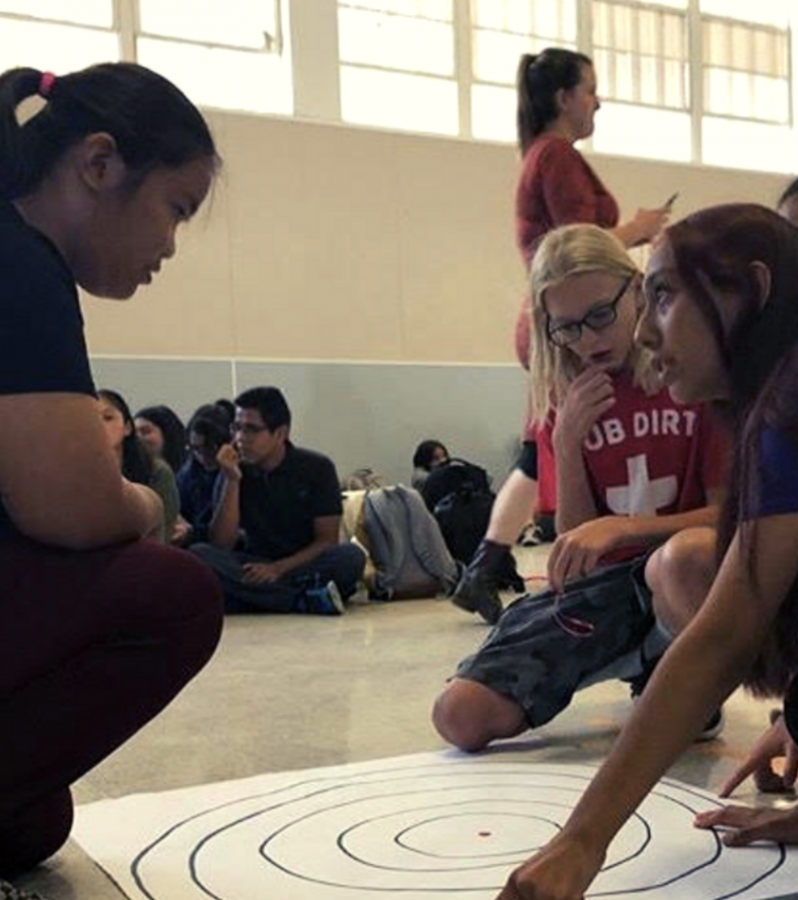 ASB Member Brittany Gutierrez explains to Francine Callanta and L.J. Patt how to participate in the Rally Game.