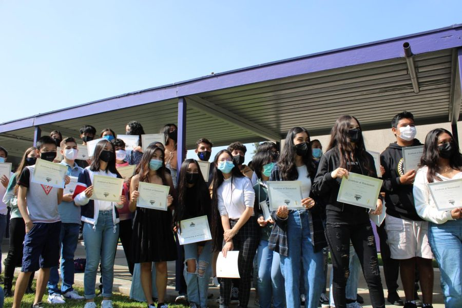The students that received the Certificate of Achievement award line up for the people of The Academy Chronicles and yearbook to take pictures.